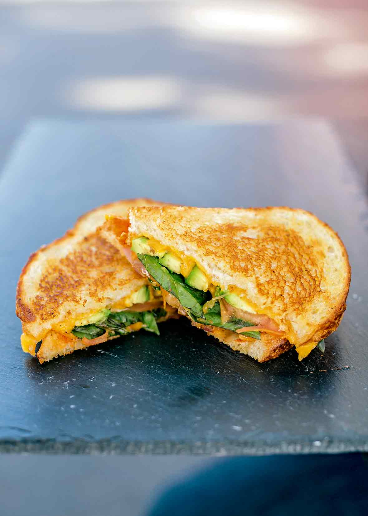A veggie grilled cheese sandwich sliced in half on a glass platter