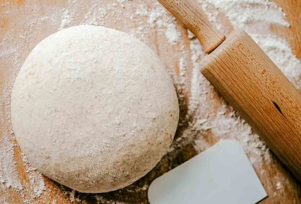 A ball of whole wheat pizza dough on a floured surface