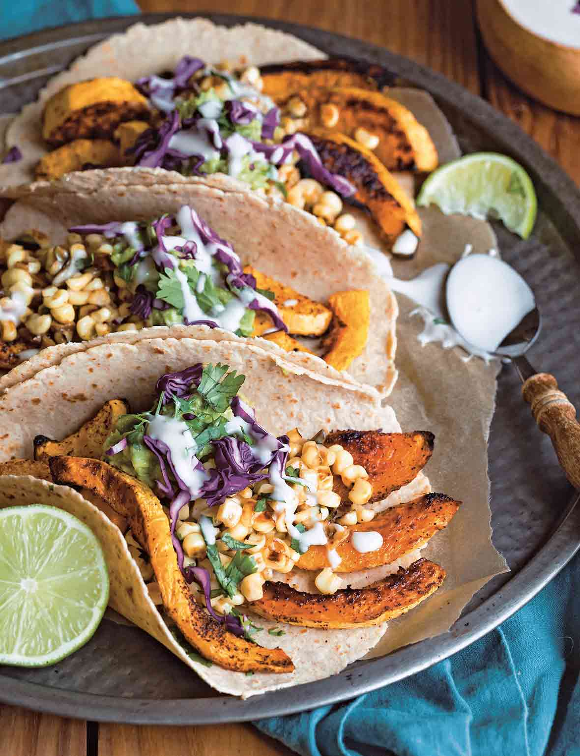 A platter of butternut squash tacos made with tortillas filled with strips of roasted squash, corn, cabbage, guacamole, and sour cream