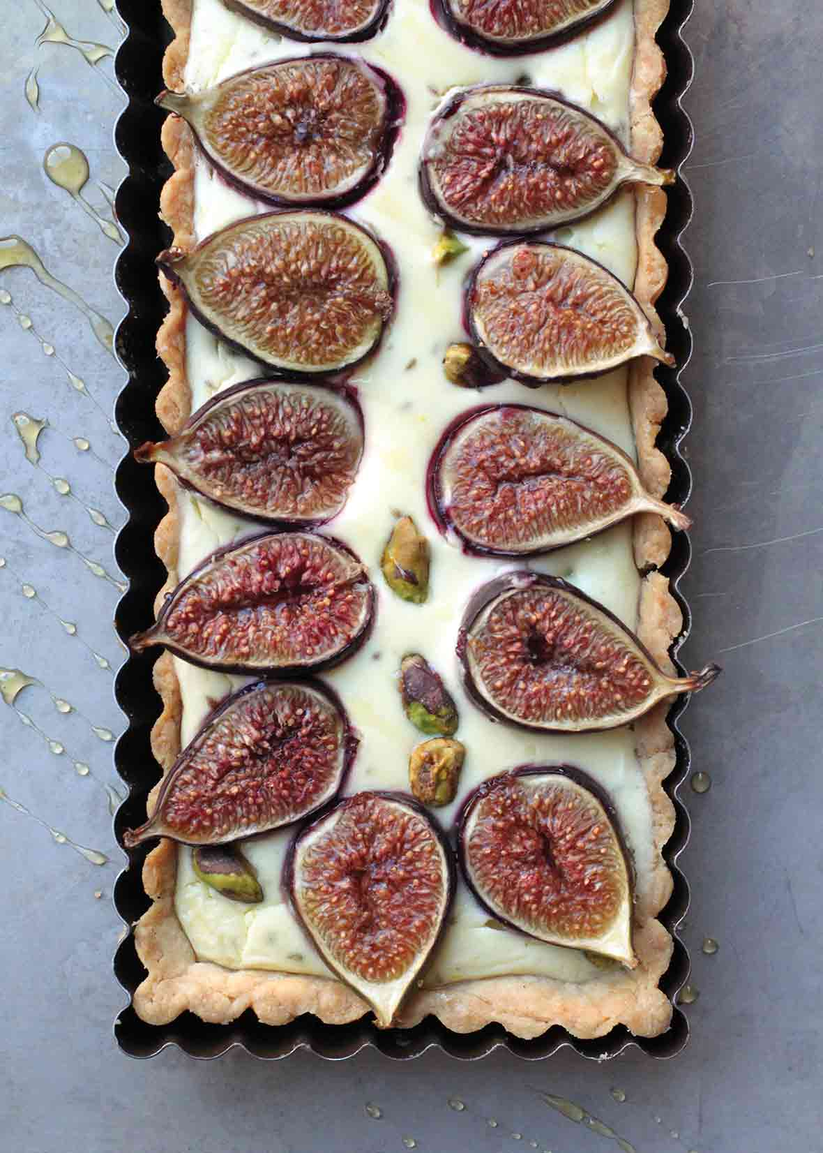 A cooked rectangular fig tart with goat cheese and pistachios in a tart pan