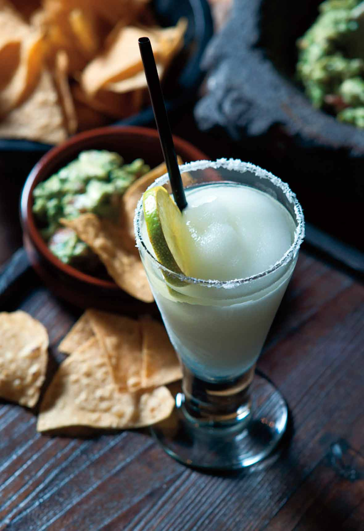A tall glass of frozen margarita with a salt rim and lime wheel beside a bowl of chips and guacamole