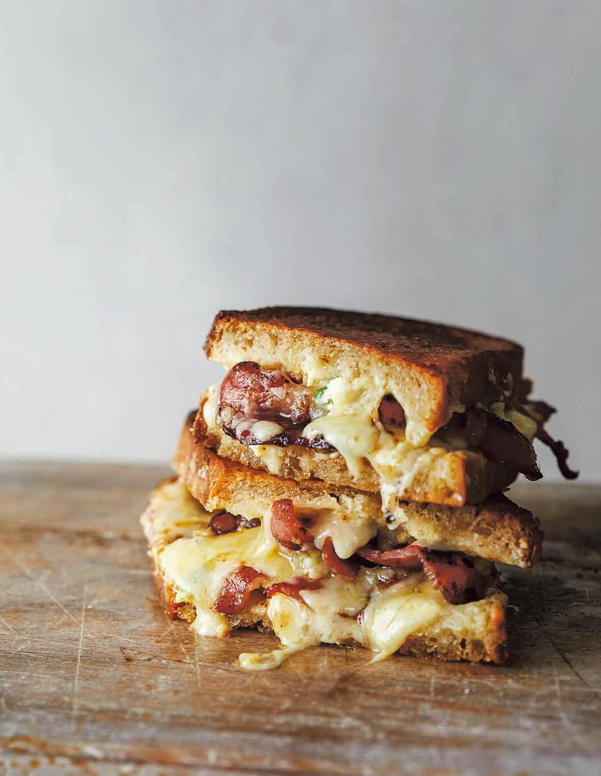 Two halves of grilled cheddar jalapeno popper sandwich stacked on top of each other