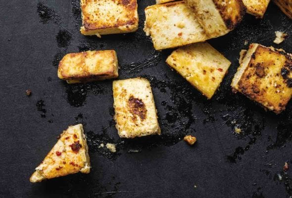 Several irregularly shaped pieces of miso glazed tofu on a black slate background