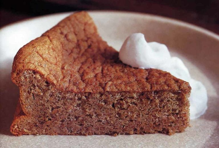 A slice of pecan torte with bourbon whipped cream dolloped on the side