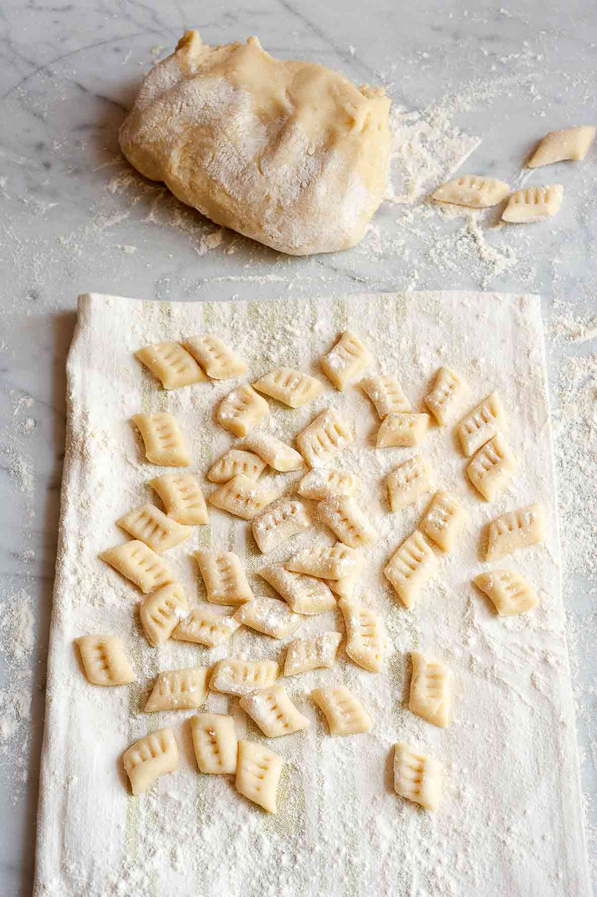 Many prepared potato gnocchi on a floured kitchen towel, with a mound of gnocchi dough in the background