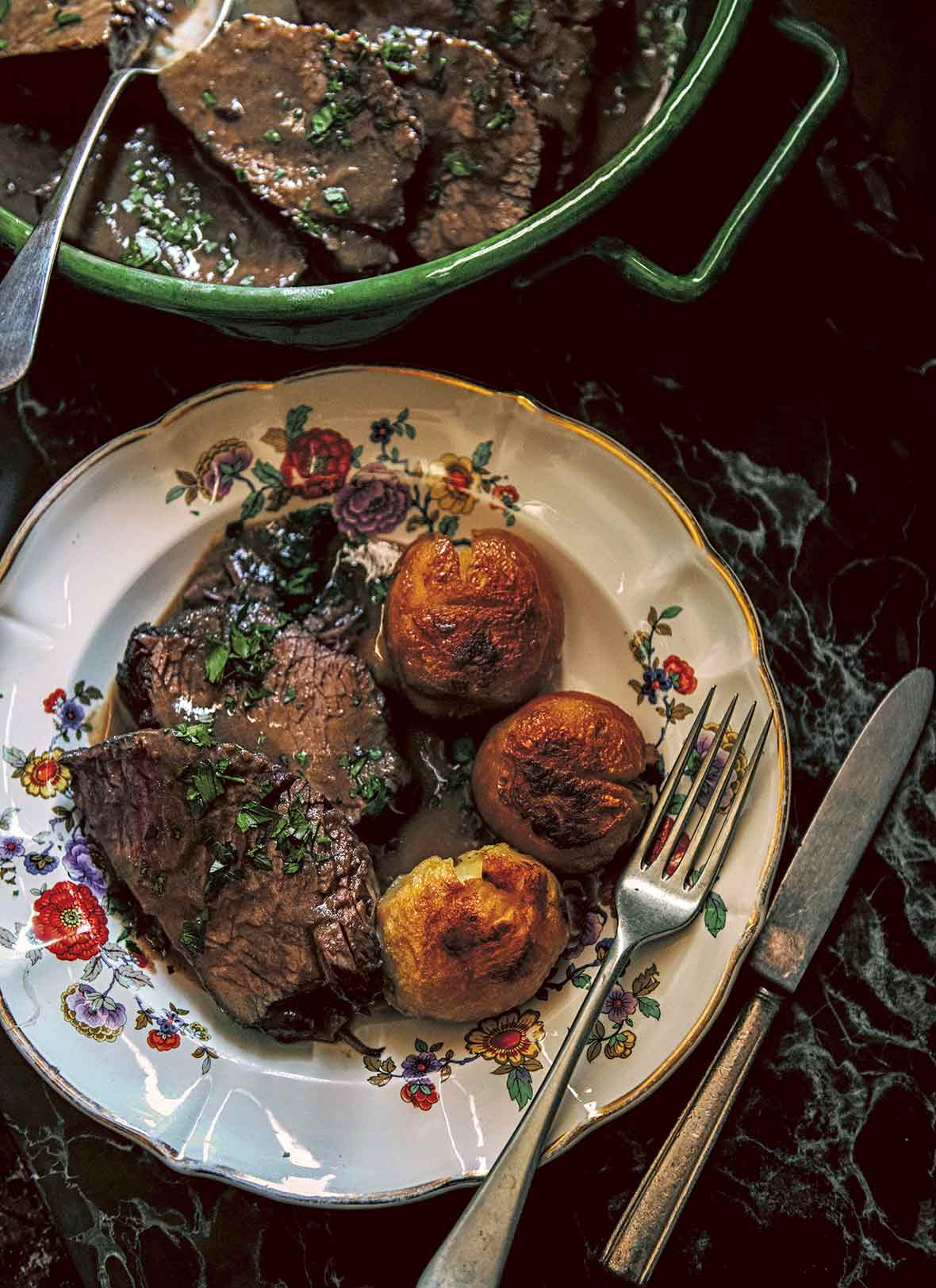 A china plate with three slices of beef braised in red wine and sprinkled with parsley, and three roasted potatoes