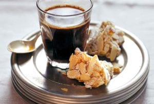 Two pieces of Rosa's almond biscotti on a stack of plates with a glass of coffee