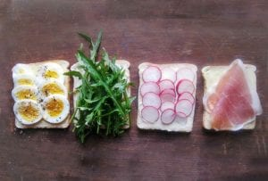 Tea sandwiches being assembled with four slices of bread topped with sliced egg, arugula, radish, and prosciutto