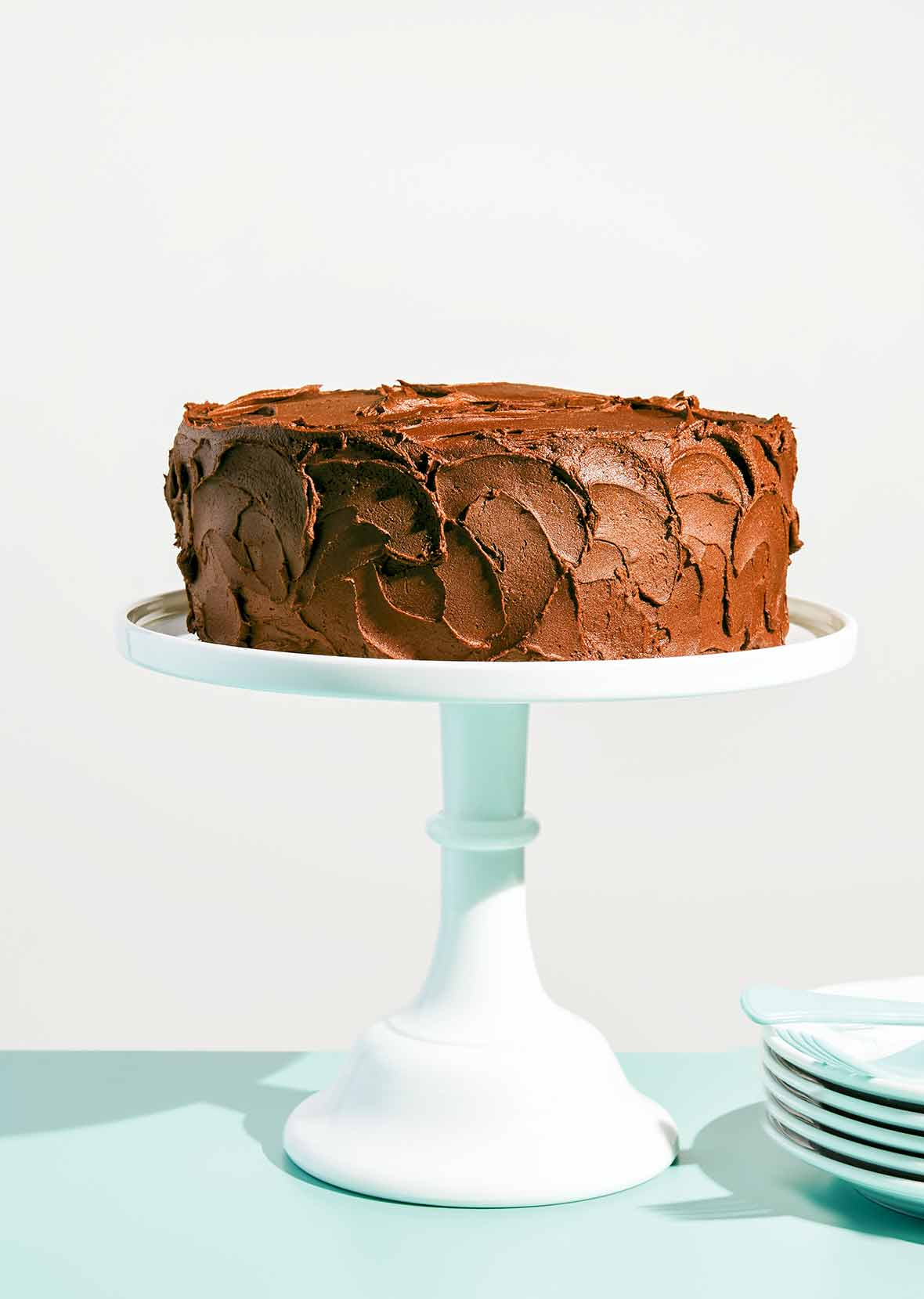 A yellow cake with chocolate frosting on a white cake stand