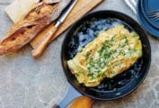 A black skillet containing a cheese omelet, topped with chives and Gruyere
