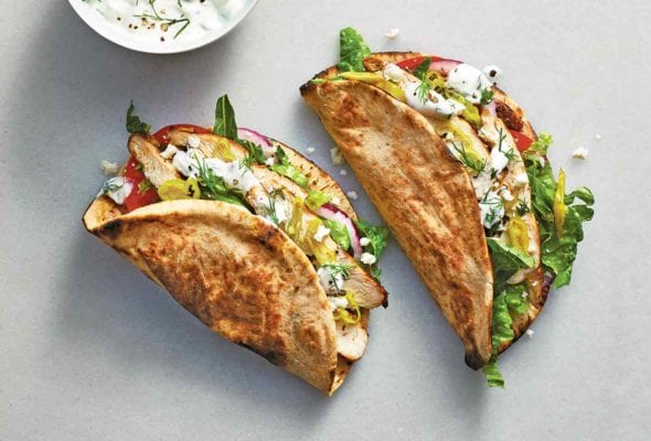 Two chicken gyros filled with chicken, red onion, romaine, tomato, and tzatziki with a bowl of tzatziki beside them.