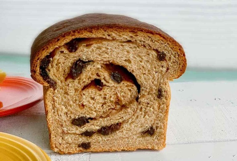 A loaf of cinnamon raisin swirl bread cut in half so the swirl is visible.