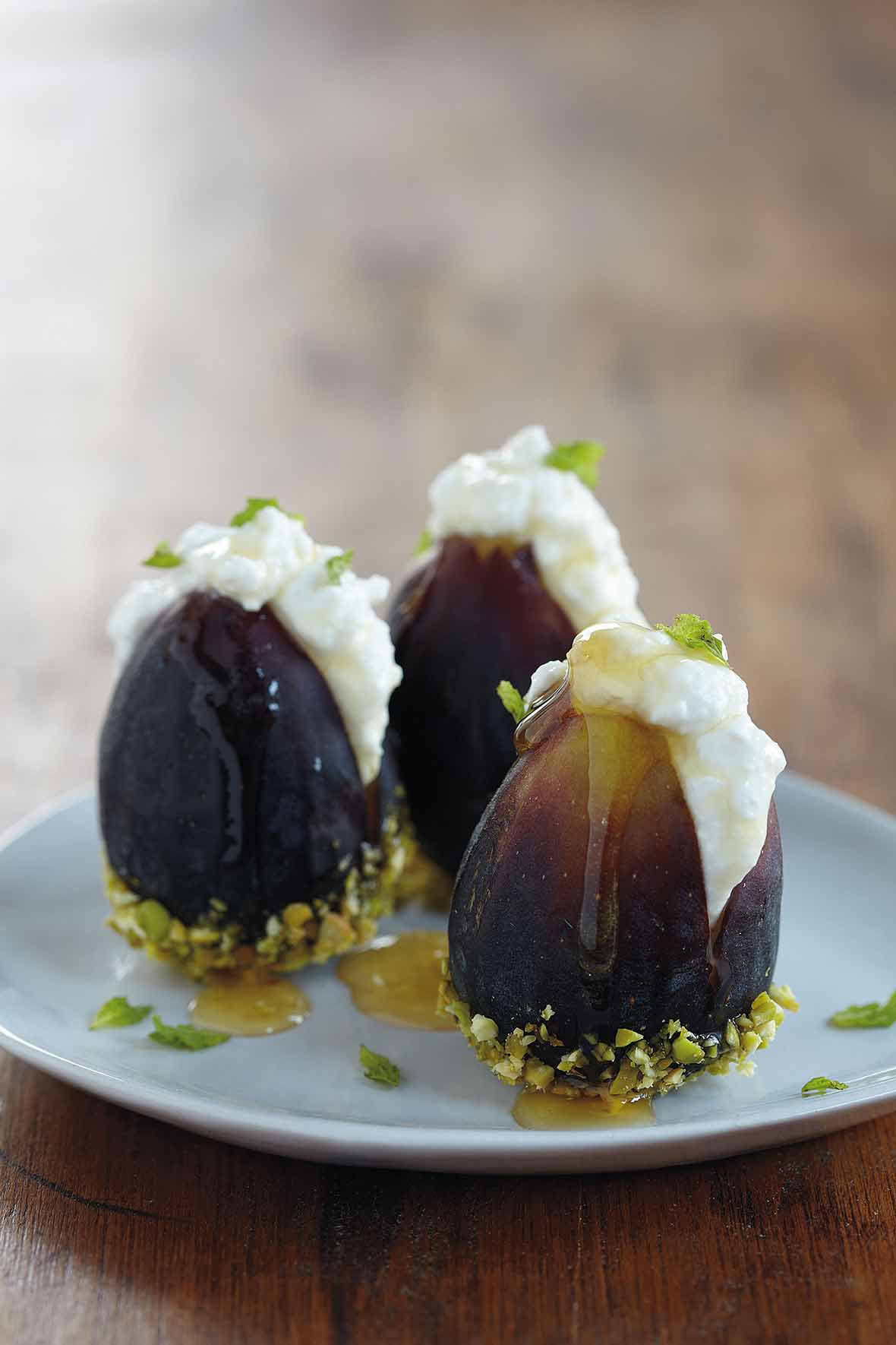 Three fresh figs with ricotta and honey and dipped in pistachios on a white plate