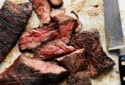 A sliced grilled steak with coffee spice rub and a carving knife lying beside it