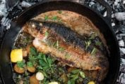 A grilled whole trout in a cast-iron skillet with sliced potatoes, parsley, and lemon