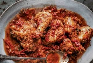 A grey platter of Italian-style chicken braised in wine with a spoon resting on top
