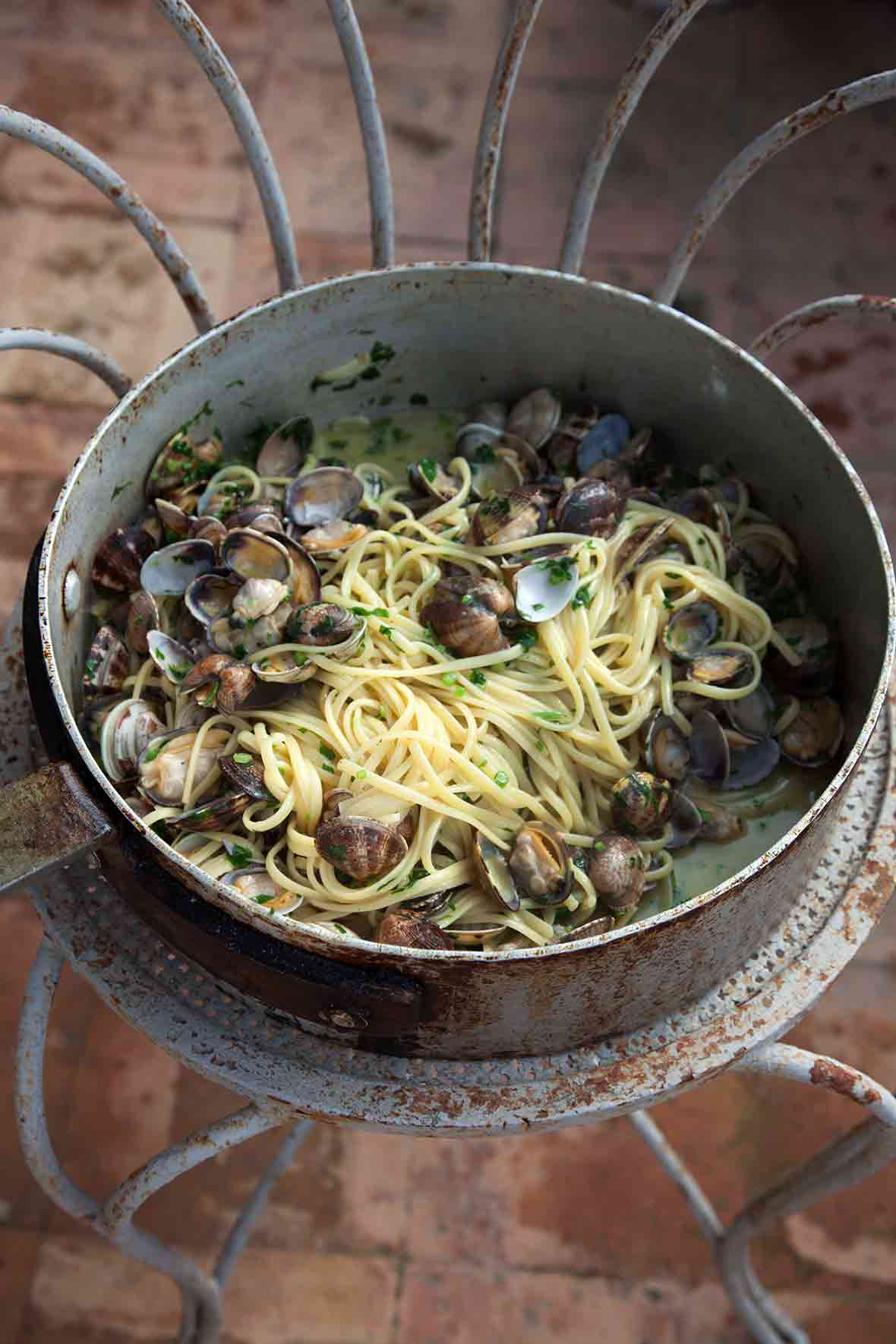 A large metal pot filled with linguine with clams resting on a metal stand