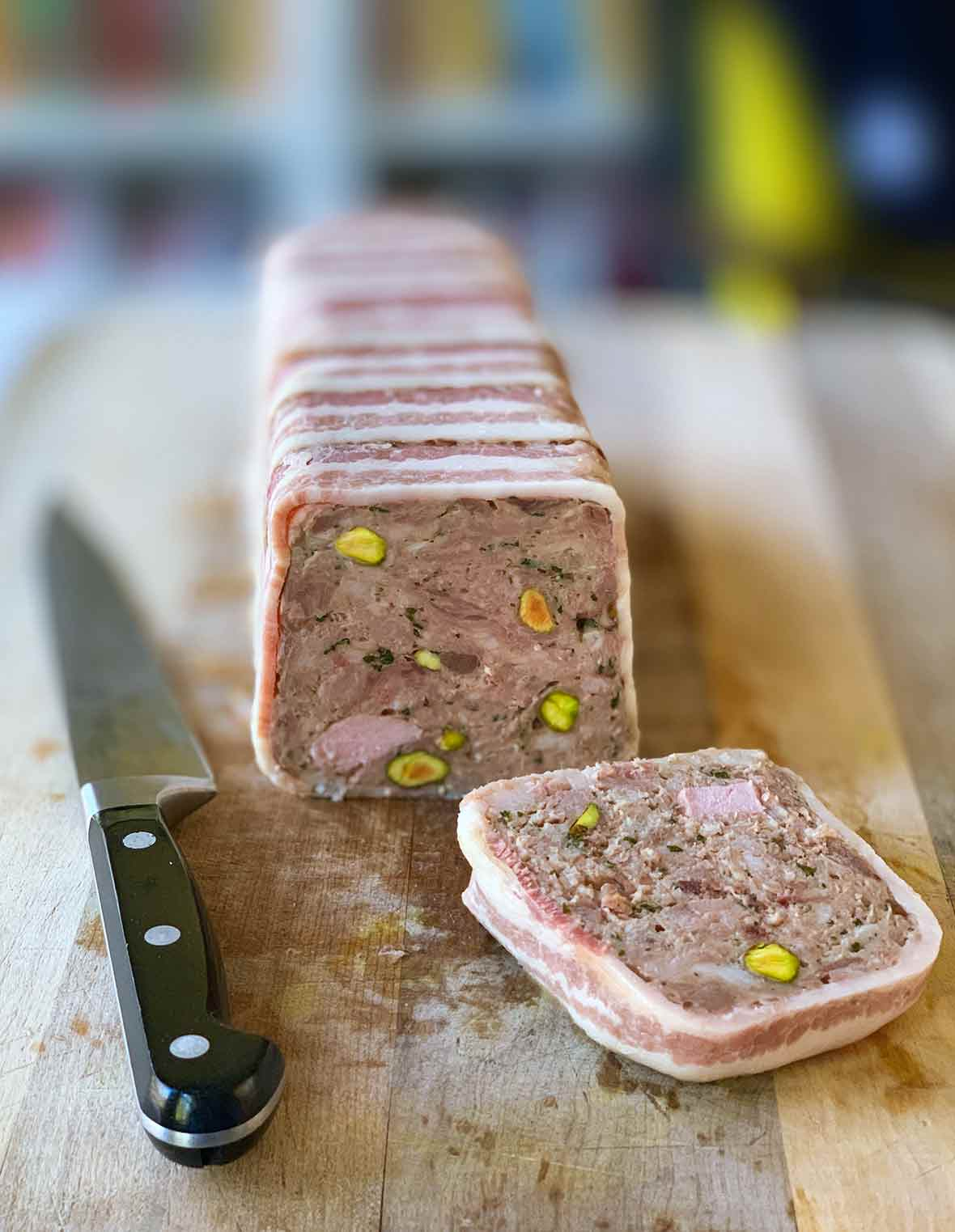 A terrine of country pate with one slice cut and resting on a wooden cutting board with a knife beside it