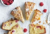 Nine slices of raspberry peach coffee cake with a bowl of raspberries nearby and some more raspberries scattered around the cake.