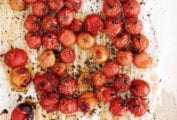 Roasted cherry tomatoes on the vine on a sheet of parchment paper