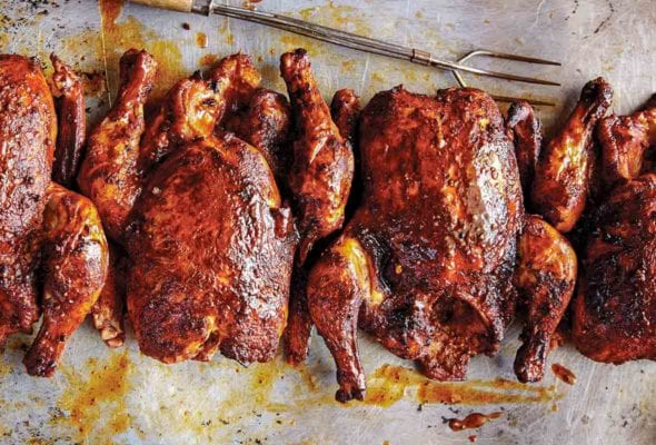 Four whole Texas smoked chickens on a baking sheet with grilling fork on the side