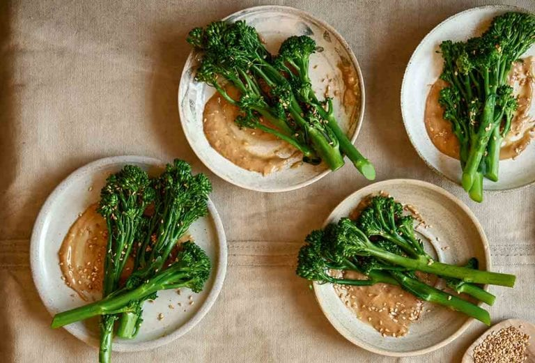 Four plates with stalks of broccoli with peanut sauce and sesame seeds.