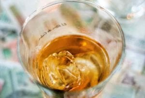 An overhead view into a glass of canchanchara with ice.
