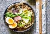 A black bowl filled with curried pork ramen, jammy egg, bok choy, sliced radish, and basil.