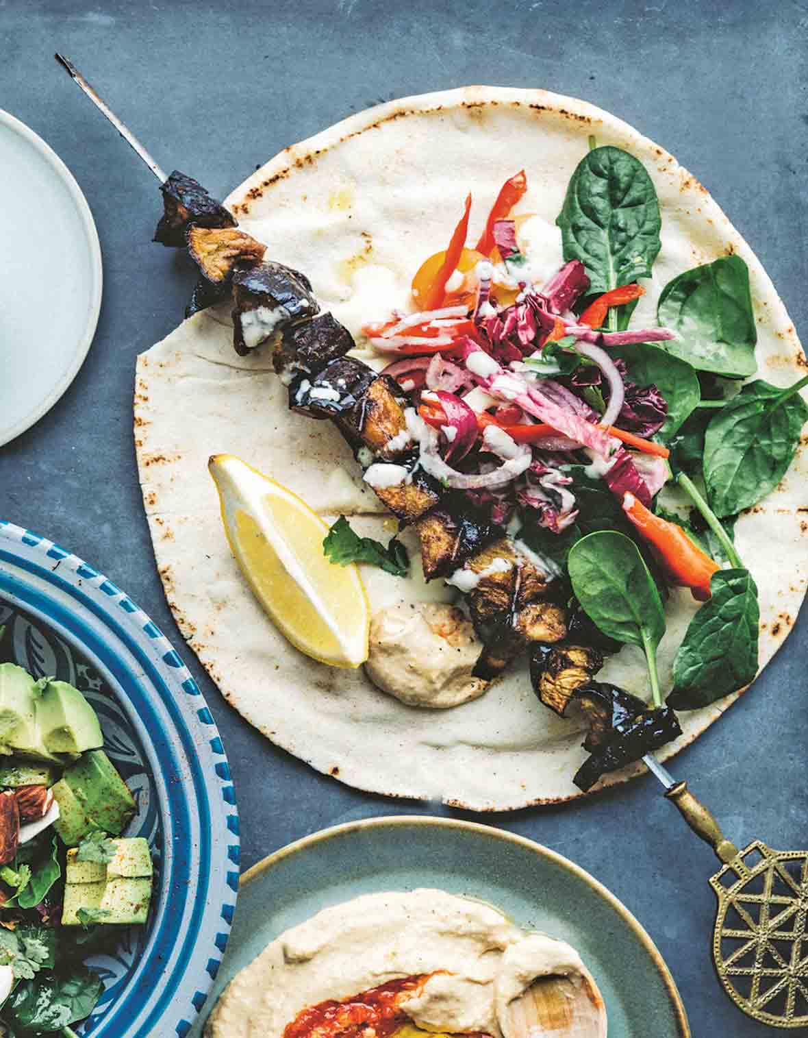 An eggplant kebab on a pita with a lemon wedge, garlic sauce, spinach leaves, red onion, cherry tomatoes, red pepper, and cabbage.