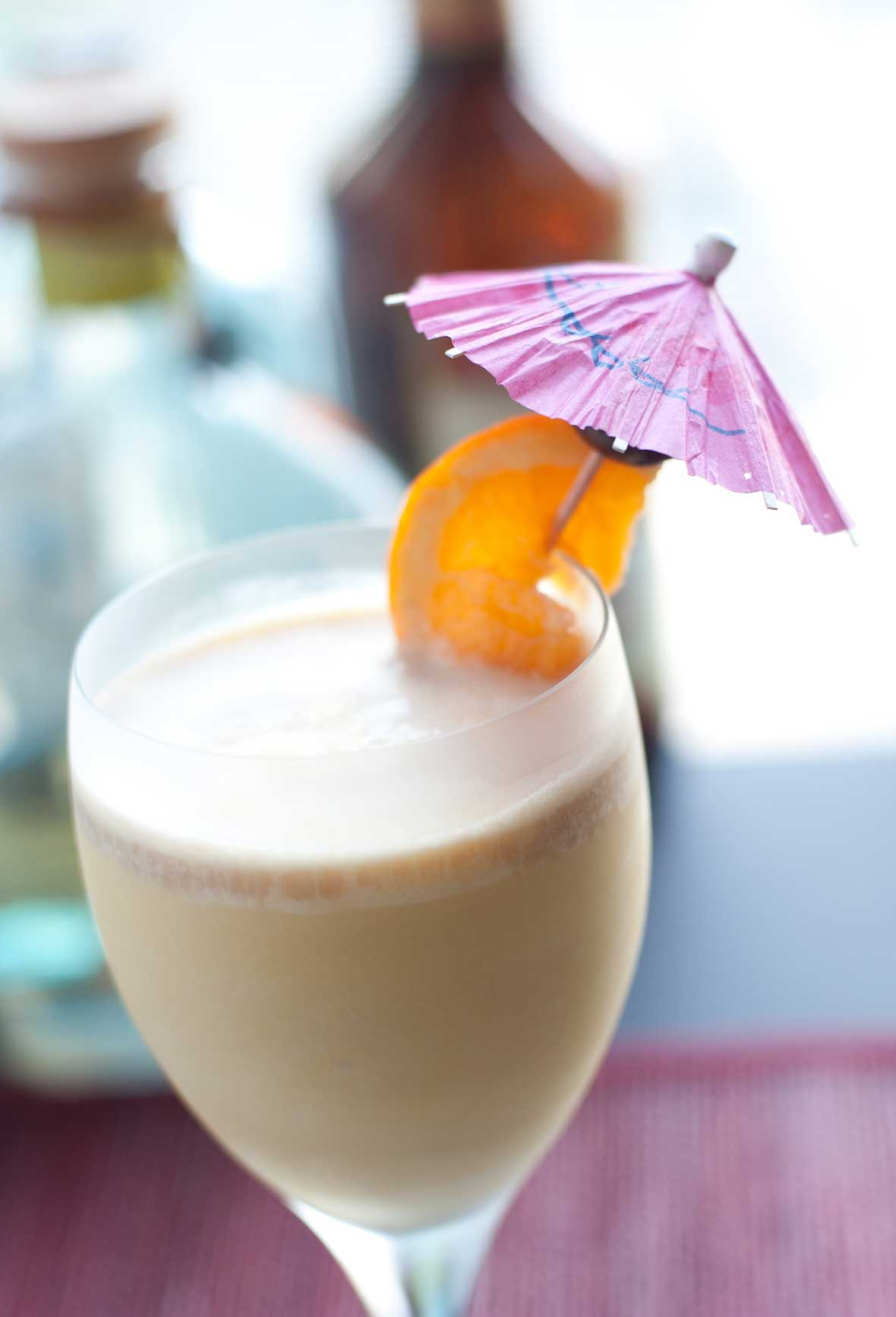 A wine glass filled with frozen Long Island iced tea, garnished with an orange slice on an umbrella.
