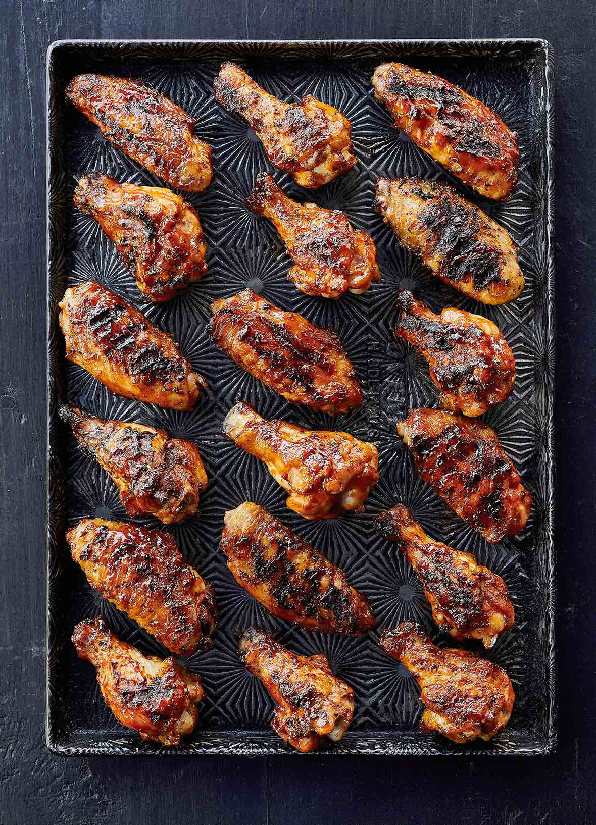 A rimmed baking sheet with 18 grilled chicken wings with maple bourbon sauce.