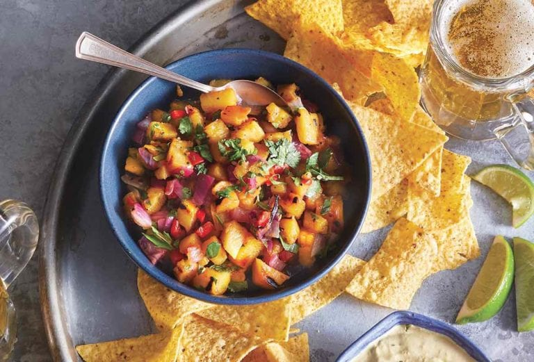 A blue bowl filled with grilled pineapple salsa on a platter with tortilla chips., beer, and lime wedges.
