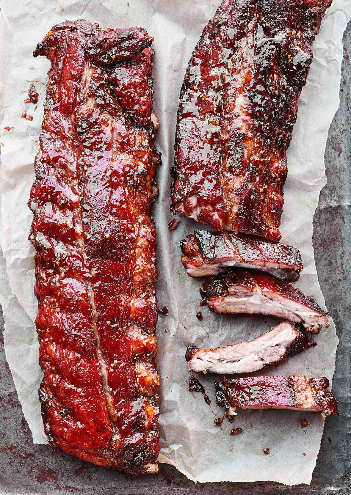 Two slabs of honey teriyaki ribs, one partially cut into ribs on a sheet of parchment.
