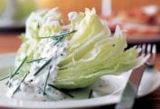 A white plate topped with an iceberg wedge with blue cheese dressing.