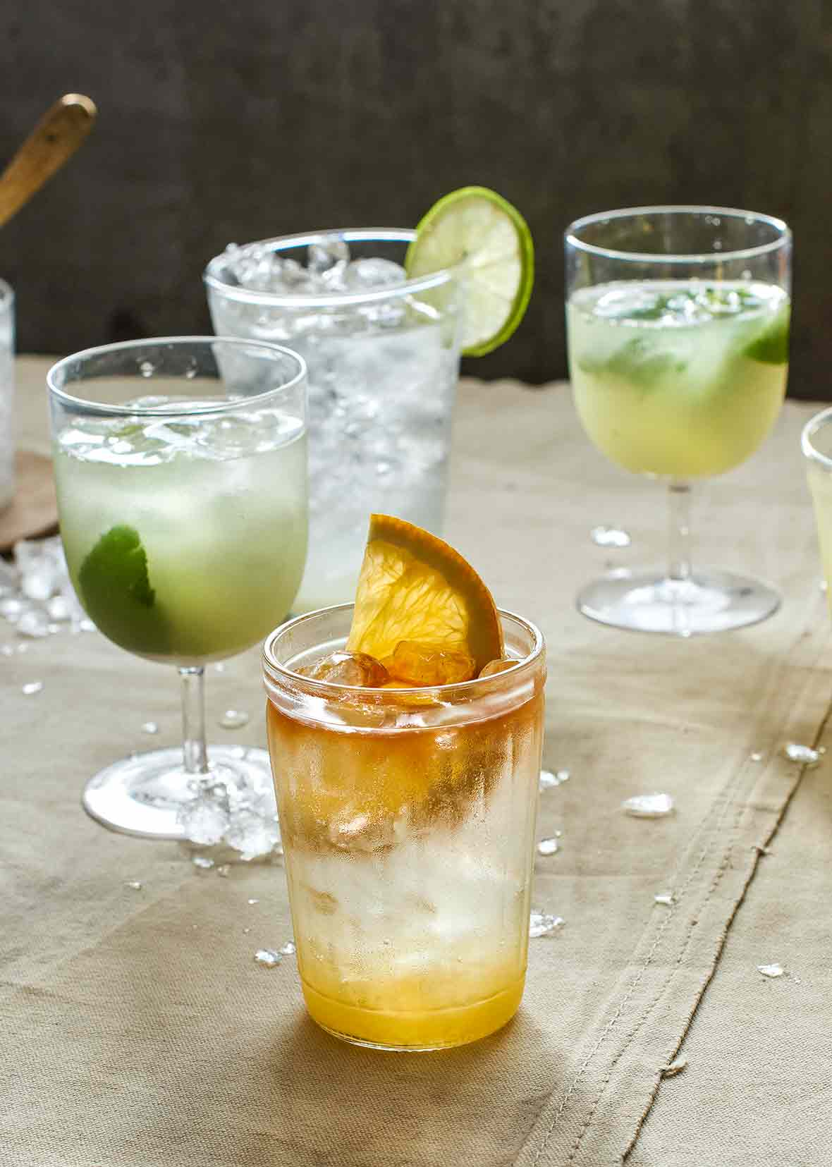 Two glasses of lime soda and one glass of angostura orange.