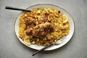 A white oval platter filled with couscous that is topped with Middle Eastern chicken thighs, lemon slices, and chopped parsley.