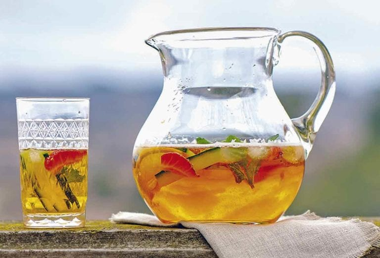 A pitcher of Pimm's cup, with a half-filled glass and a vase of flowers on either side of it.