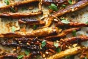 A rimmed baking sheet filled with roasted carrots with apricot glaze, chopped almonds, and torn mint.