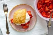 A strawberry shortcake on a pink plate with a bowl of strawberries and a bowl of cream beside it.