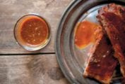 A platter of ribs covered with Texas-style barbecue sauce, and a glass of extra sauce on the side.