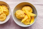 Three bowls of vegan mango ice cream topped with mango slices.
