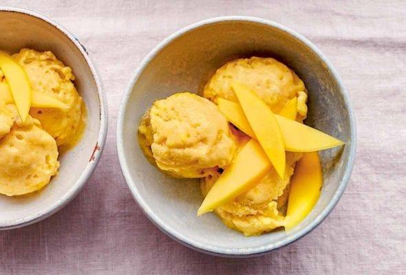 Three bowls of vegan mango ice cream topped with mango slices.