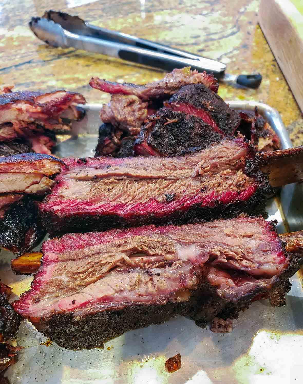 Individual smoked beef ribs on a baking sheet.
