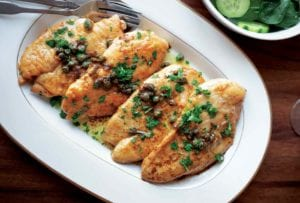 A white serving platter with four pieces of classic chicken piccata topped with capers and chopped parsley.