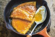 A small orange skillet with two crêpes Suzette and a spoon topped with citrus sauce.
