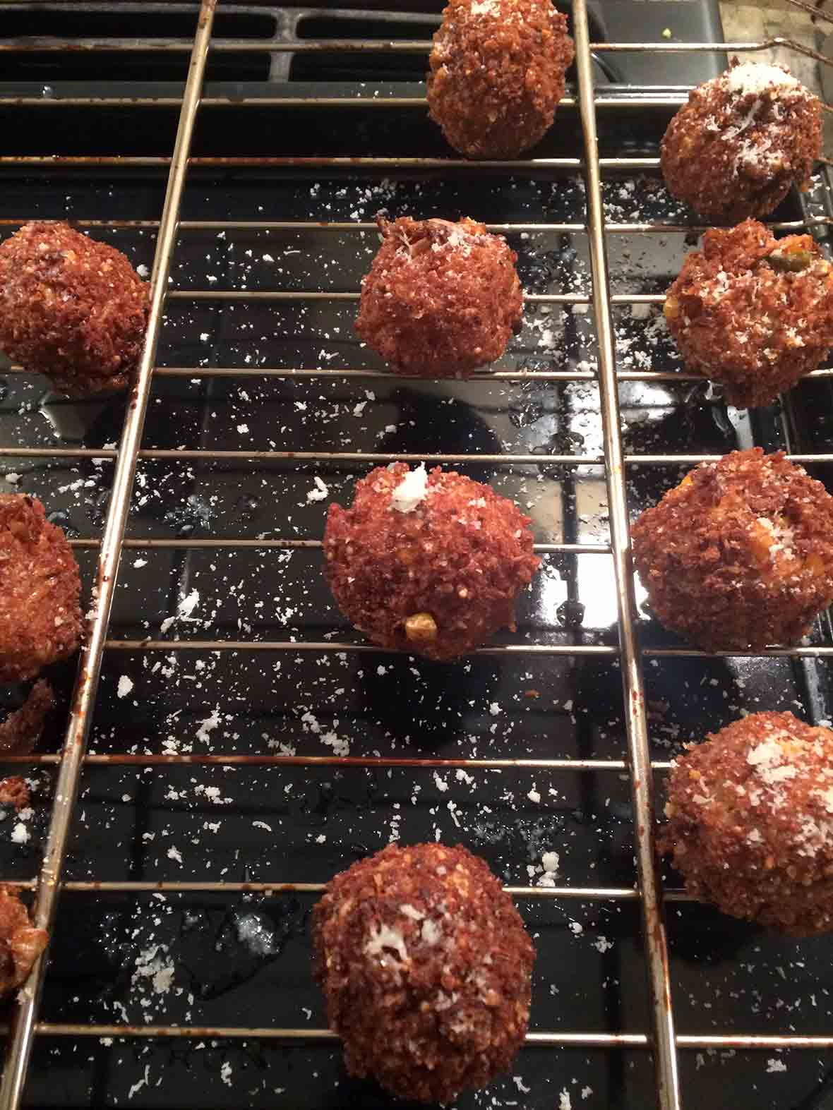 Ten deep-fried kimchi arancini on a wire cooling rack.
