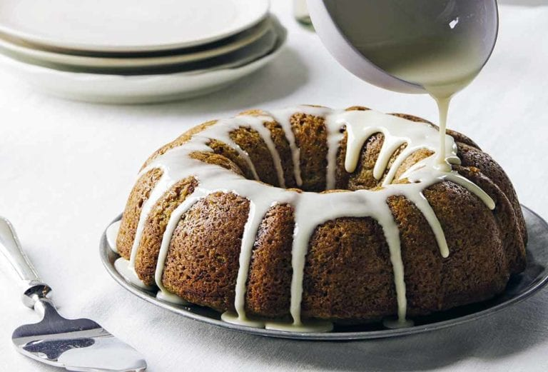 An old-fashioned zucchini cake on a silver plate with lemon glaze being drizzled over it.