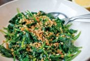 A white serving bowl filled with sauteed spinach and bread crumbs.