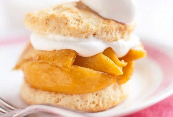 A spiced peach shortcake on a white plate with spiced peaches layered between two biscuit halves and topped with whipped cream.