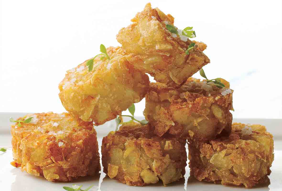 A stack of six homemade tater tots, sprinkled with sea salt.